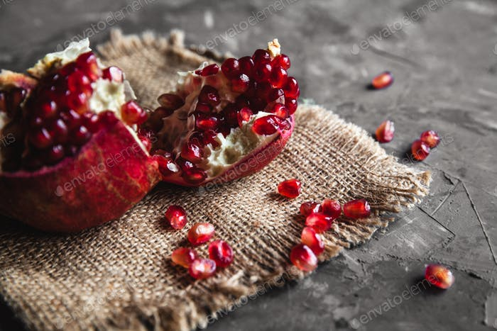 Juicy tasty pomegranate with burlap on a dark background. Delicious food, fruit