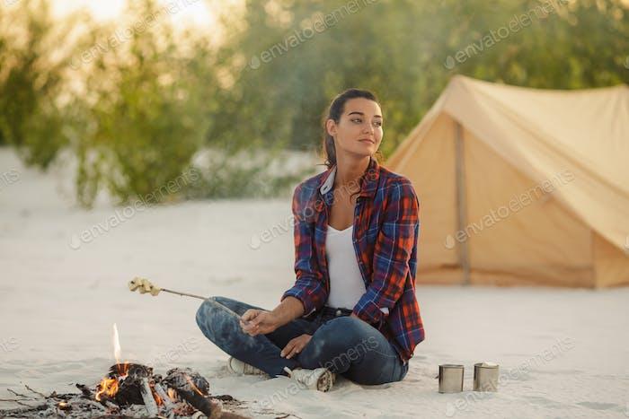 Frau Camping In der Nähe von Lagerfeuer