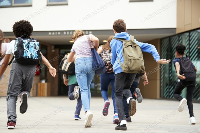 Group Of High School Students Running Into School Building At Beginning Of Class