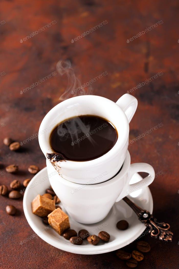 Kaffeetasse mit Kaffeebohnen und braunem Zucker auf braunem Steinhintergrund. Copyspace für Ihren Text