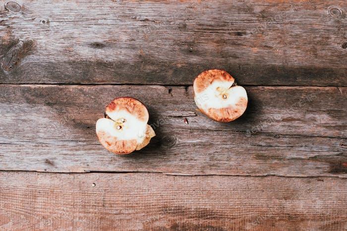 Verdorbener schlechter roter Apfel auf hölzernem Hintergrund. Müllkippe faules Essen. Draufsicht. Kopierraum. Verfaulte