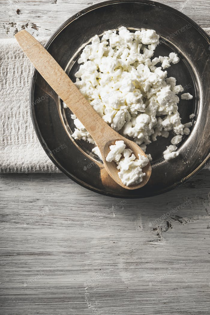 Fresh cottage cheese with wooden spoon on the  metal plate on the white wooden table vertical