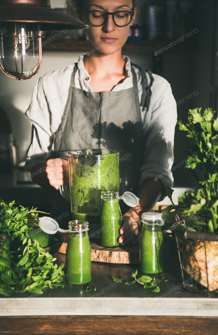 Young female making green take-away smoothie in kitchen