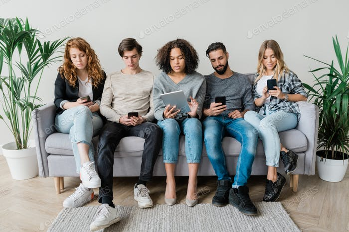 Five young contemporary casual friends sitting on couch in row by wall