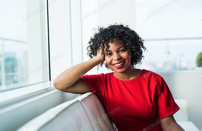 A portrait of woman sitting on a sofa by the window in an office.