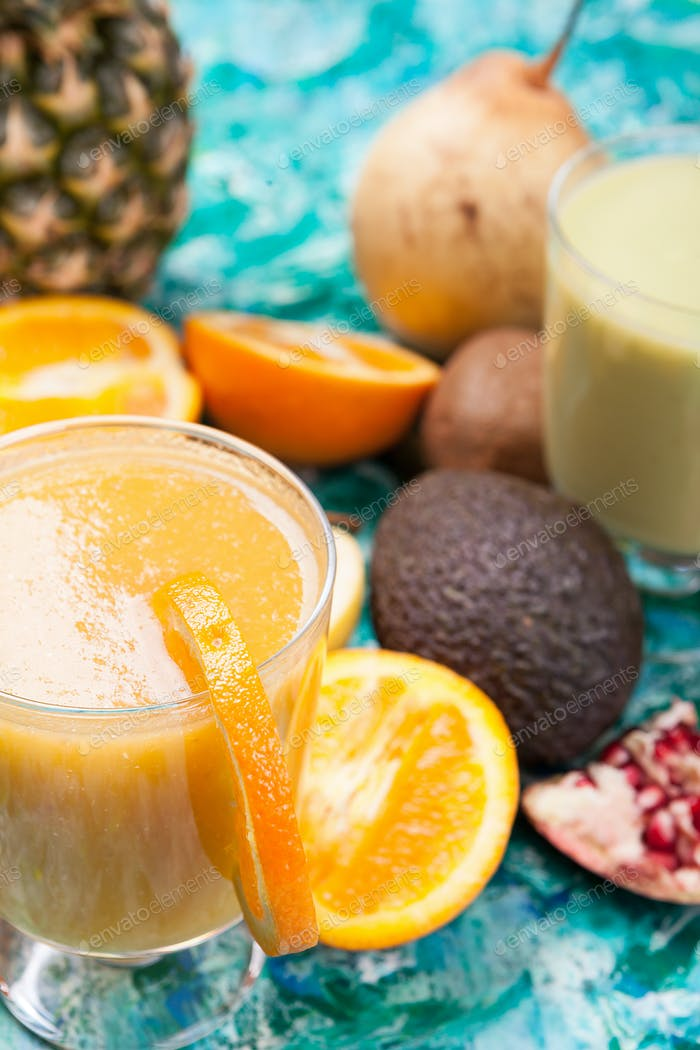 Glasses with detox smoothie surrounded by fruits