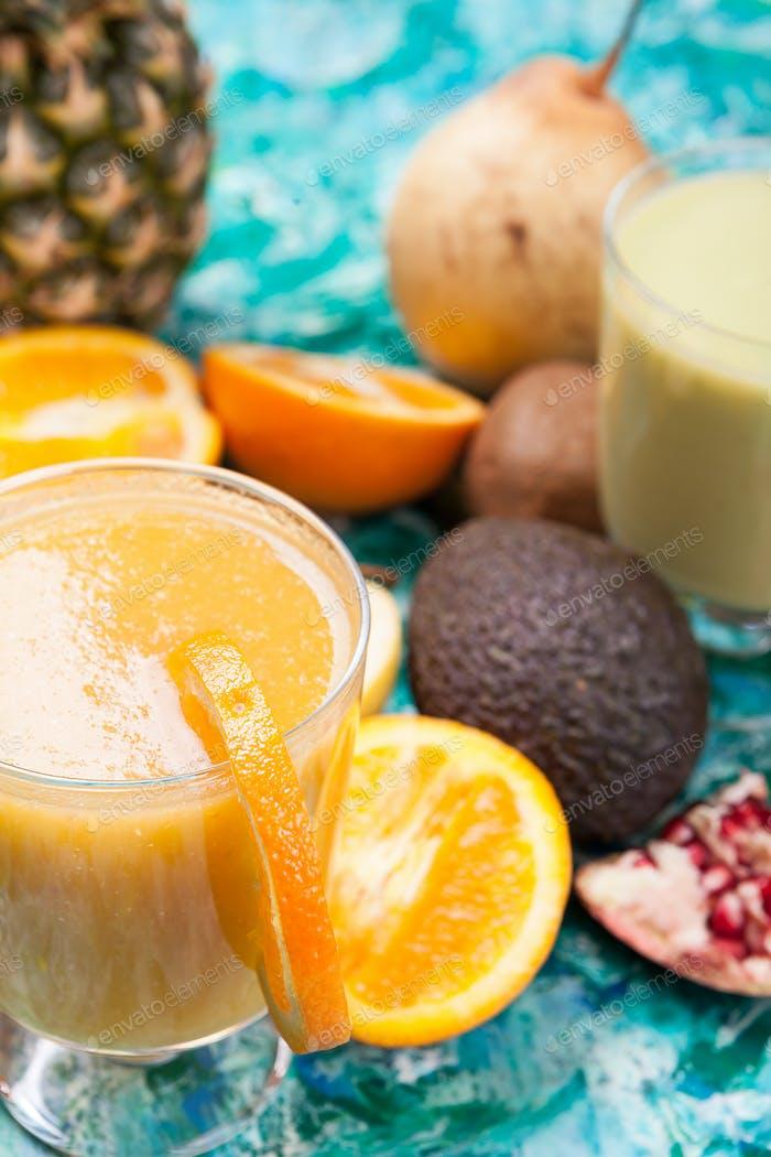 Gläser mit Detox-Smoothie umgeben von Früchten