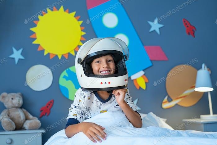 Kid spielt Astronaut in seinem dekorierten Schlafzimmer