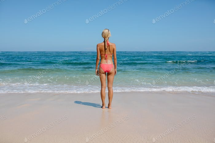 Young woman in bikini on serene beach