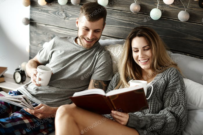 Happy young couple with coffee reading in bed