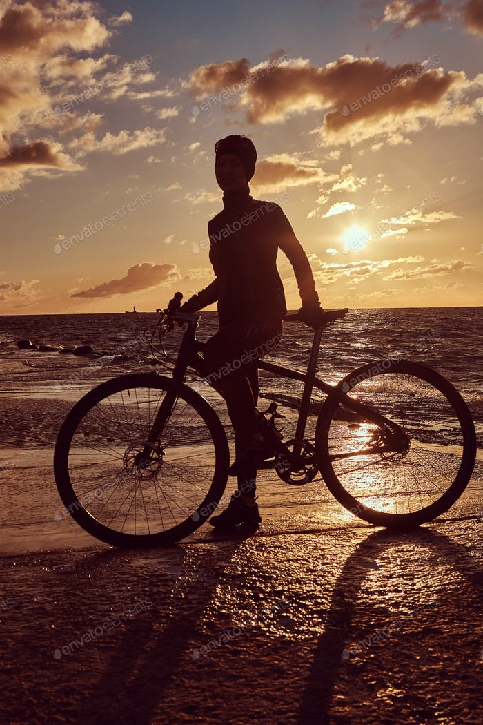 Female cyclist standing with her bicycle and enjoying the sunset on the sea coast.