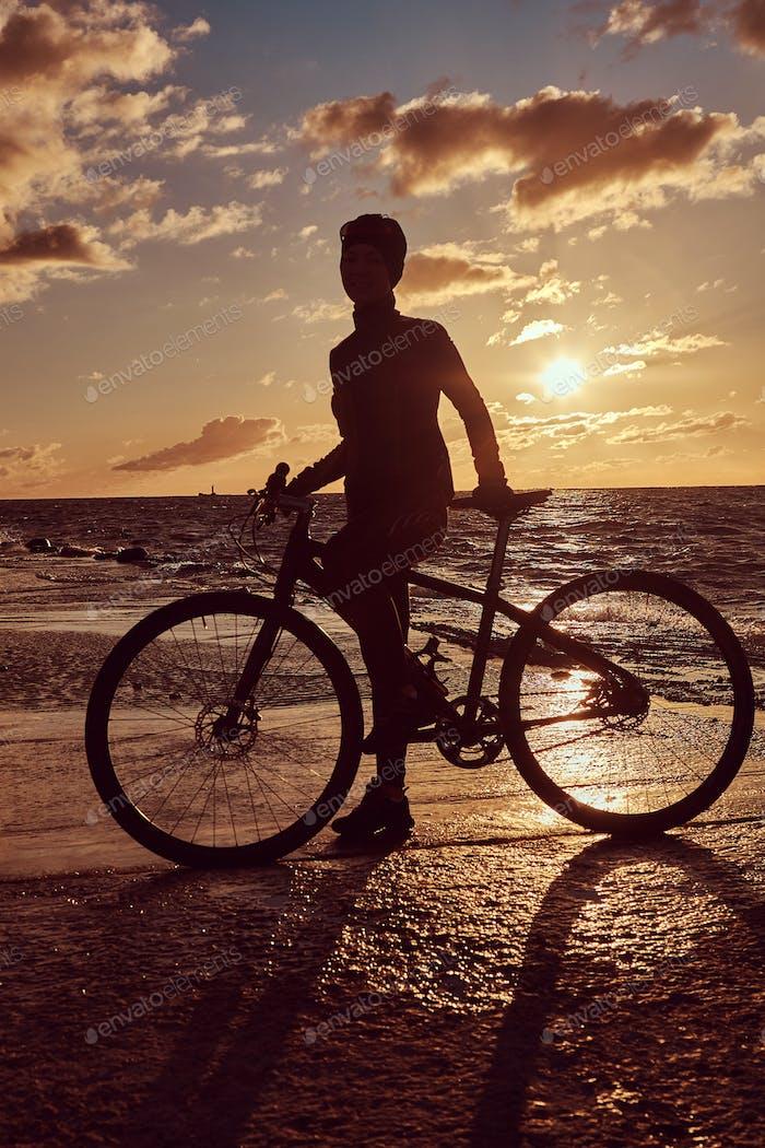 Ciclista femenina de pie con su bicicleta y disfrutando de la puesta de sol en la costa del mar.