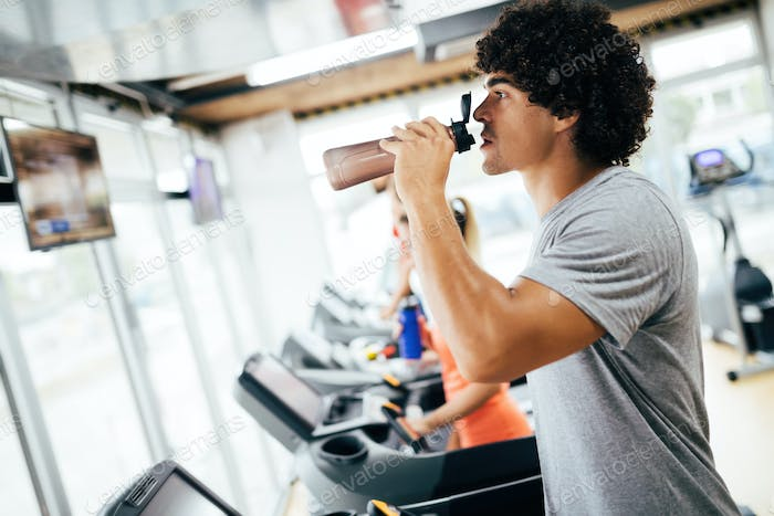 Young handsome man doing cardio training in gym