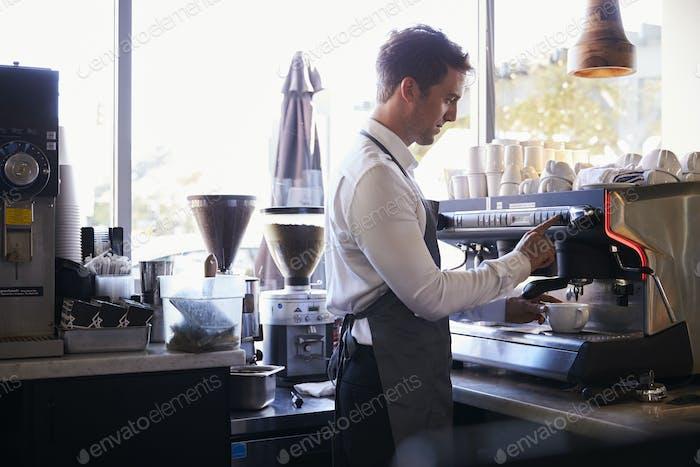 Barista Making Coffee In Delicatessen Using Machine