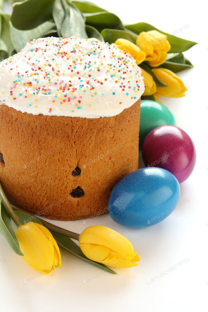 Easter bread, colorful eggs and yellow tulips on white background