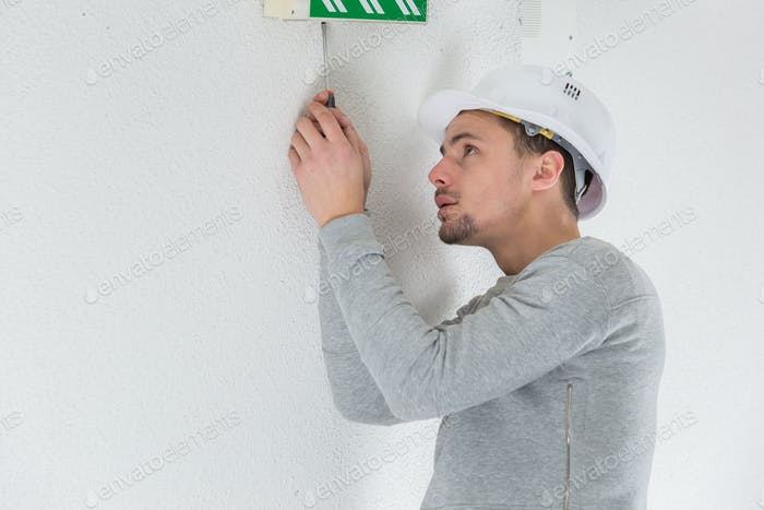 a male electrician fixing electric sign on the ceiling