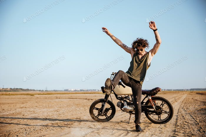 Man making dust standing near his motorcycle