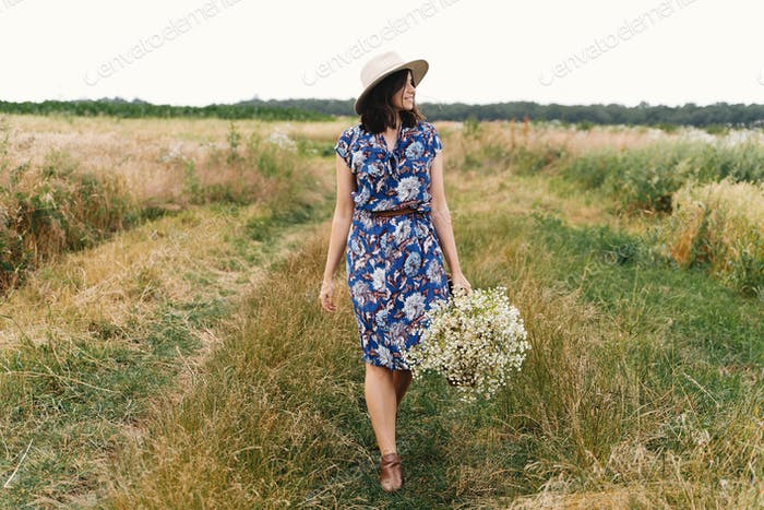 Stylish young woman in blue vintage dress and hat walking with white wildflowers