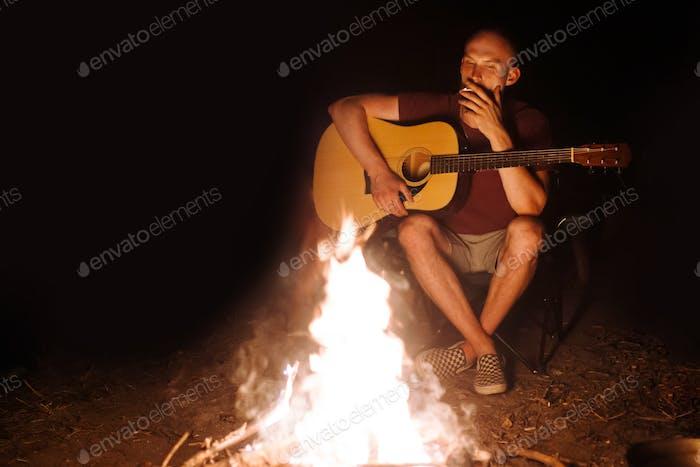 Hipster man smoking cigarette and holding acoustic guitar at big bonfire at camp