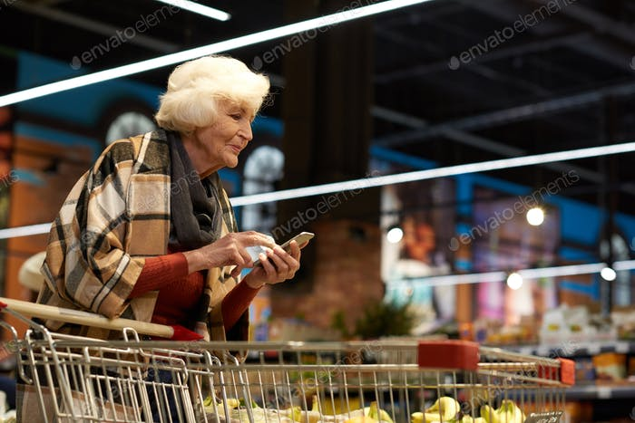 Senior Woman Using Smartphone in Supermarket