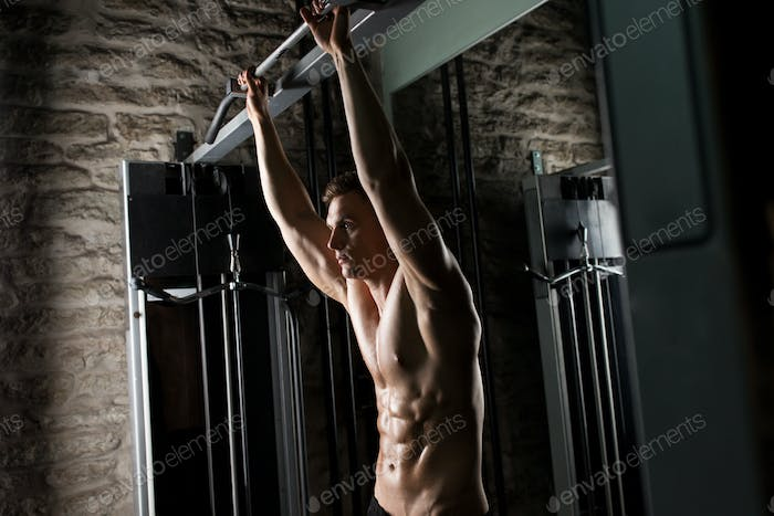 young man exercising with pull-up bar in gym