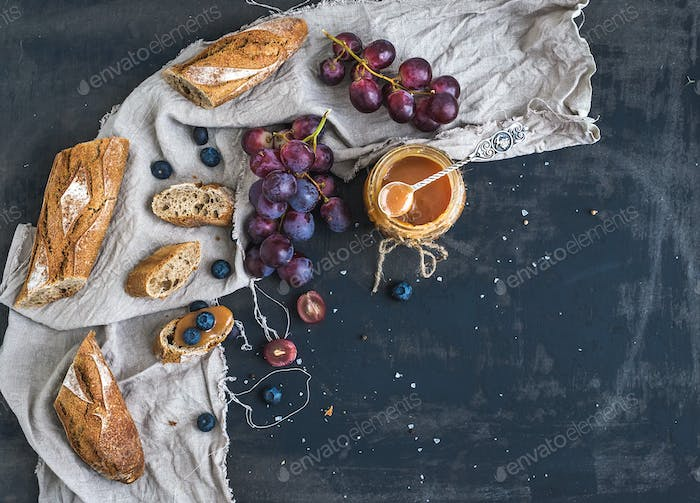 French baguette cut into pieces, red grapes, blueberry and salt caramel sauce