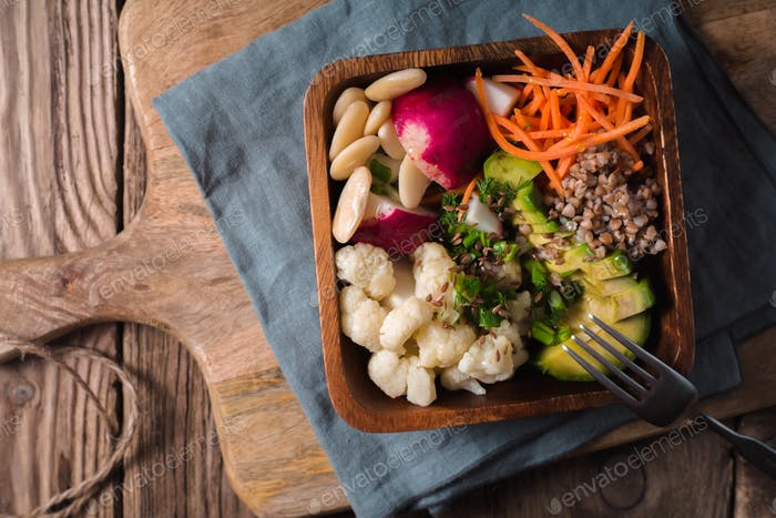 Healthy salad with buckwheat and vegetables in the wooden bowl top view