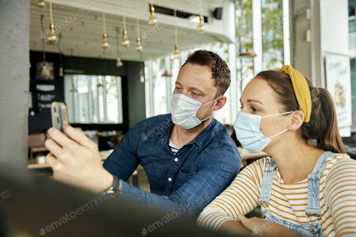 Two people wearing face masks, using a smart phone, waving during a face time call.