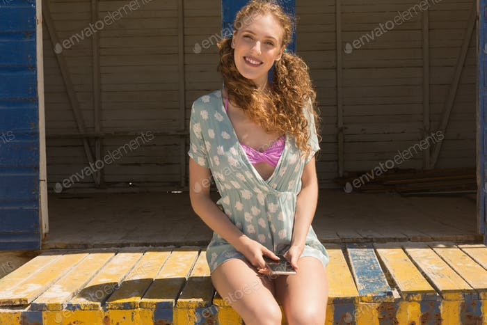 Woman with mobile phone looking at camera sitting on beach hut