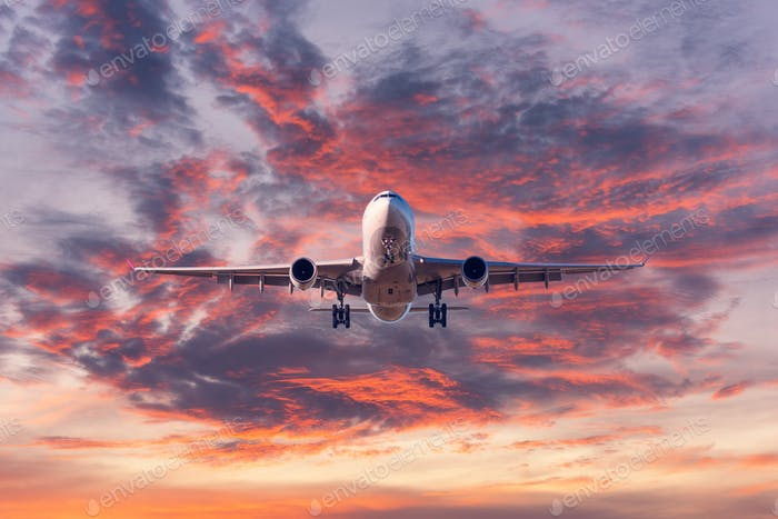 Landing passenger airplane at colorful sunset