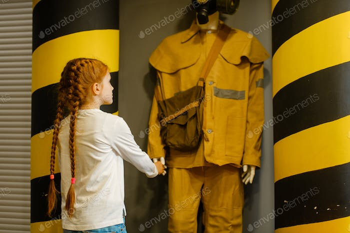 Female child looks on fireman mannequin, playroom