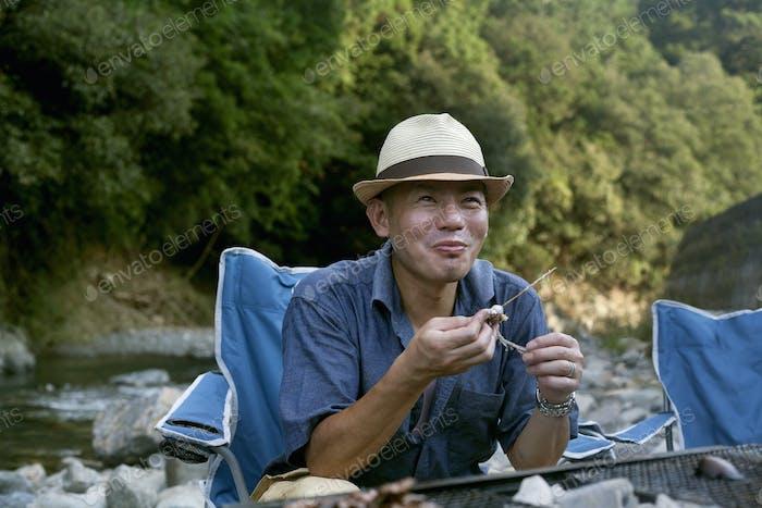 Man eating a grilled fish at a picnic.