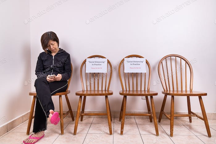 Asian woman seated next to chairs at public place with Social Distancing, Do Not Sit signage.