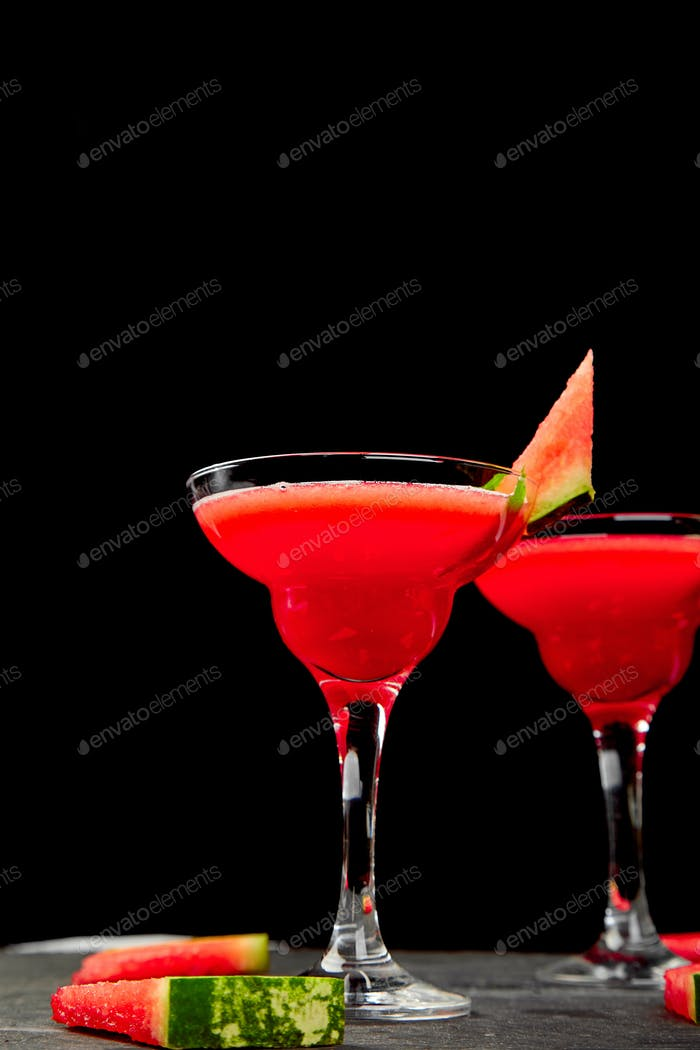Watermelon margarita cocktail on black background. Fresh watermelon lemonade