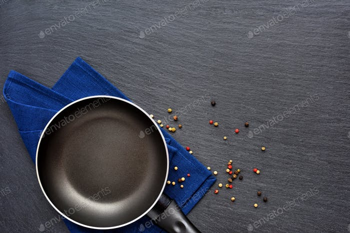 Empty frying pan with napkin and mix peppers on dark grey stone