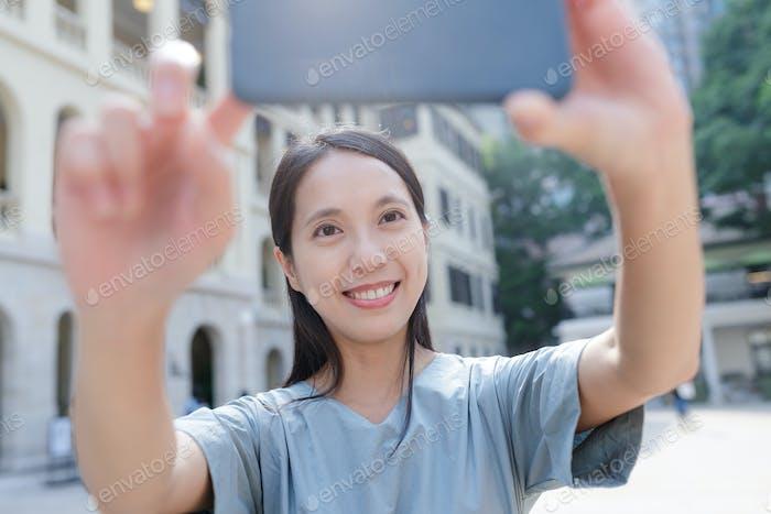 Mujer tomando selfie en la ciudad
