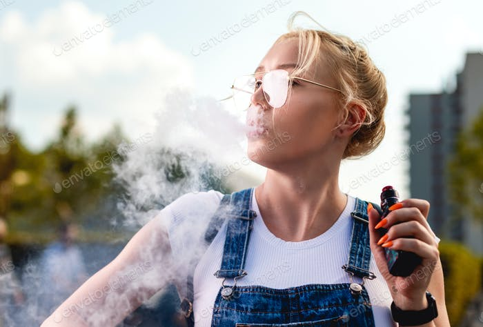 Portrait of young woman smoking an e-cigarette outdoor