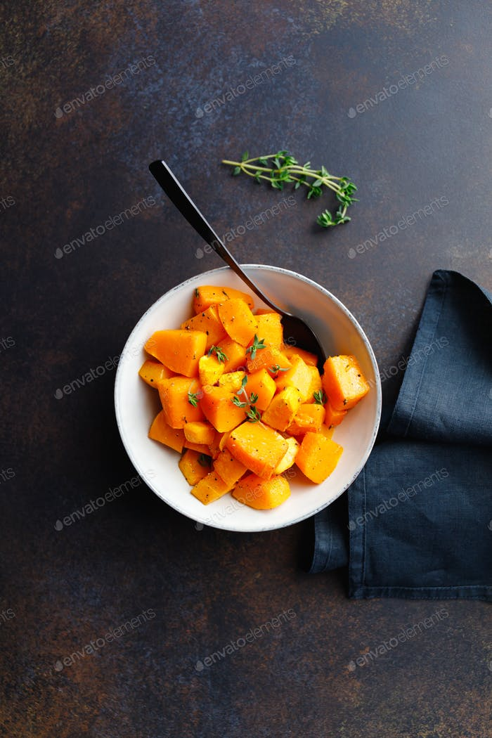 Roasted pumpkin pieces with fresh thyme in a ceramic bowl on a table. Seasonal Autumn recipe.