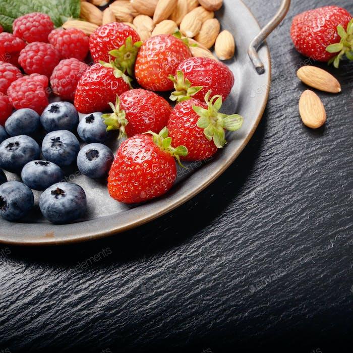 Tablett mit reifen BIO Heidelbeere Himbeere Erdbeere und Mandeln