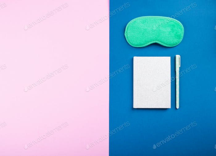Sleeping mask and sleep journal with pen on blue