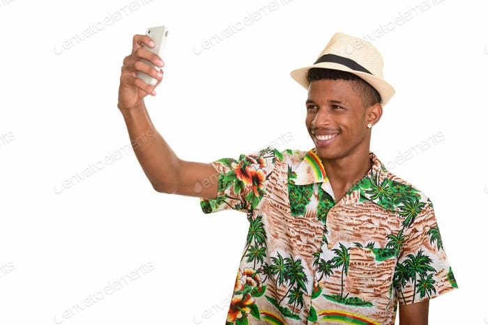 Young happy African man taking selfie with mobile phone ready fo