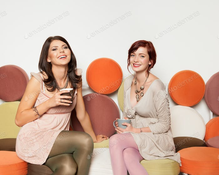 attractive girls on sofa with coffee mugs laughing