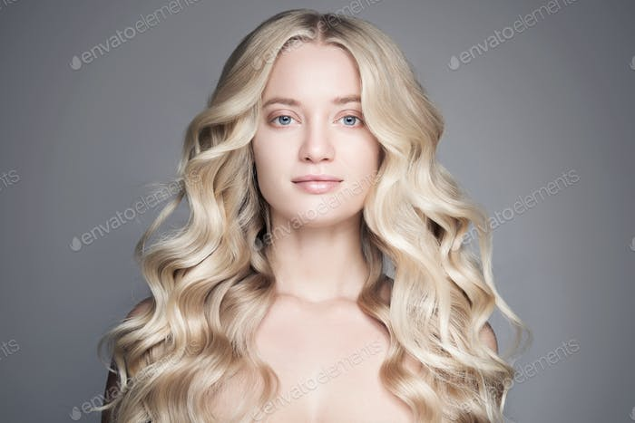 Portrait Of A Beautiful Young Blond Woman With Long Wavy Hair.
