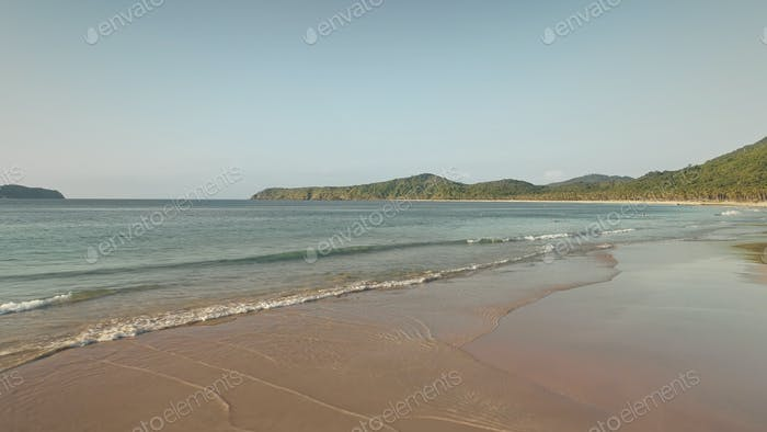 Seascape at sand beach of mountain island aerial. Waves wash sandy ocean shore. Sea bay with forest