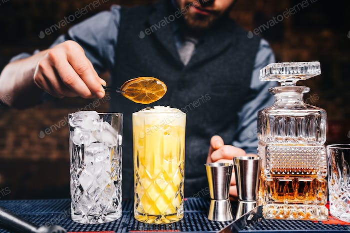 Portrait of elegant and vintage bartender, barman preparing orange based vodka cocktails