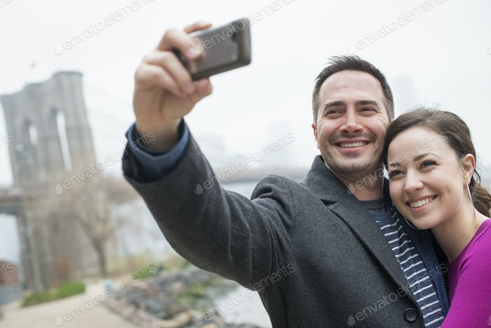 A couple taking a picture with a phone,a selfy of themselves by Brooklyn Bridge.