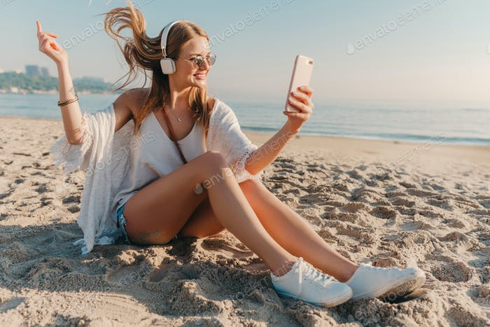 young attractive blond smiling woman on vacation sitting on beach