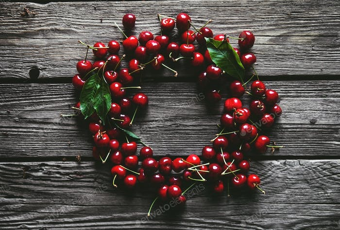 Frame, made of fresh picked cherries on rustic wooden background