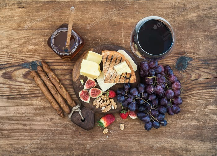 Glass of red wine, cheese board, grapes,fig, strawberries, honey and bread sticks