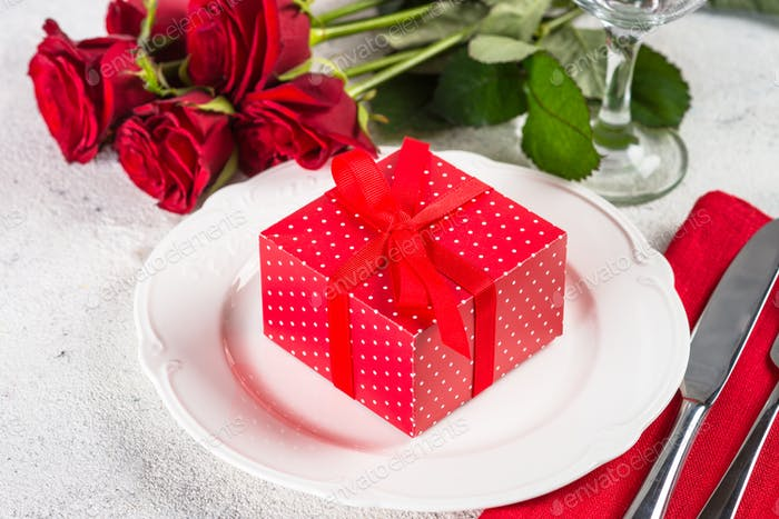 Thumbnail for Holiday table setting with plate, roses and present.